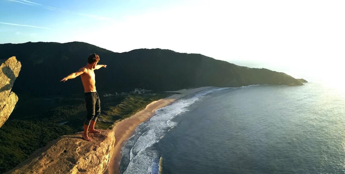 man standing on ledge with ocean below him