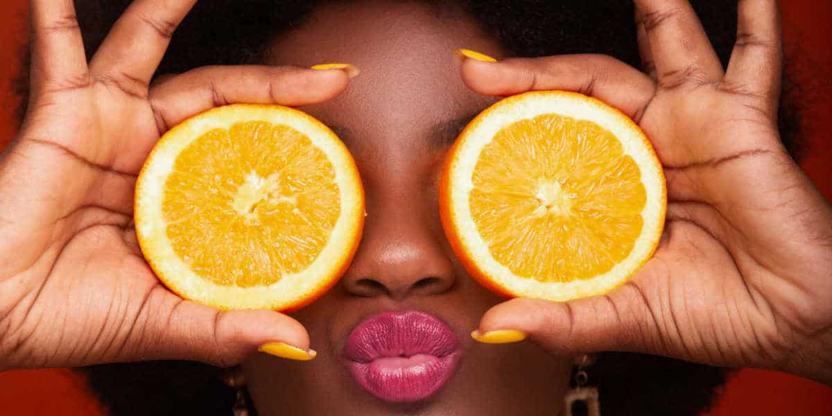 woman with oranges on eyes illustrating that vitamin C as one of the best eye vitamins