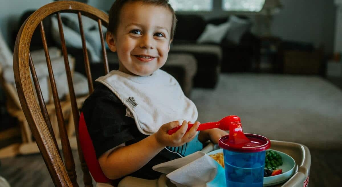 young boy sitting and eating on high chair